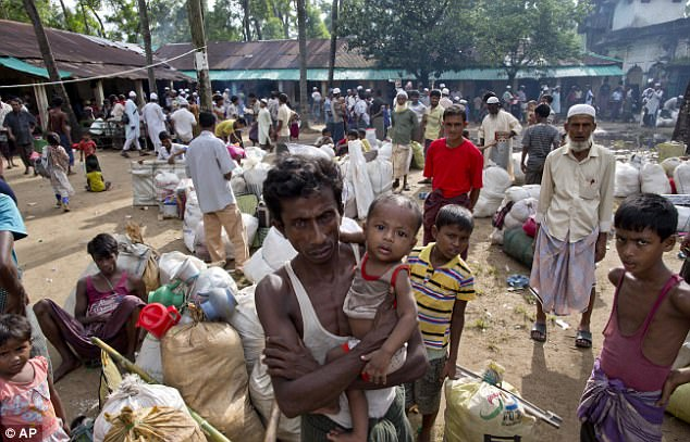 More than half a million Rohingya have fled from the Myanmar military crackdown in Rakhine State to Bangladesh after it was launched in late August. Pictured are a group of Rohingya at a transit shelter in Bangladesh
