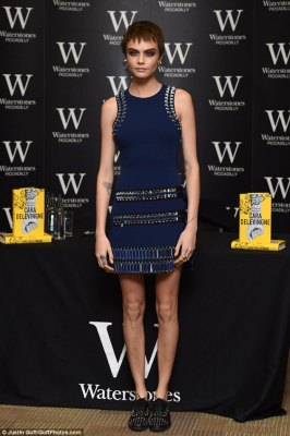 Style queen: The British beauty showcased her slender frame in a figure-hugging navy dress which boasted embellished mirror detailing throughout