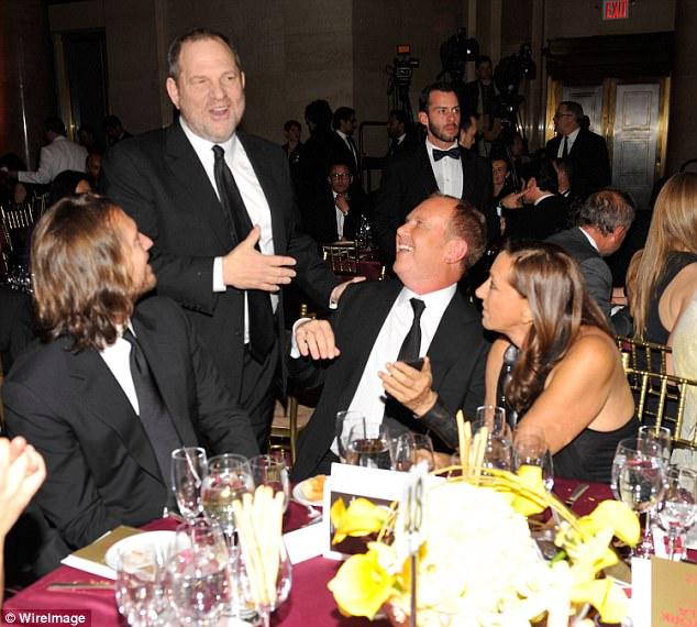 Harvey Weinstein (standing), Michael Kors (center seated) and Donna Karan (right) share a joke at the amfAR New York Gala in 2010