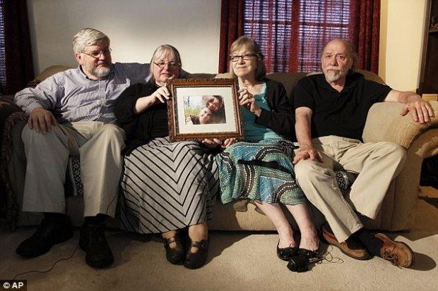 In this 2014 photograph, Caitlan's parents Lyn and Jim (right) appear with Patrick and Linda Boyle (left) holding a photograph of the couple
