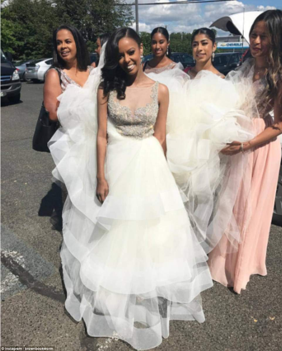 Austin's bridesmaids wore pink gowns. The bridal party pictured above holding up Austin's dress
