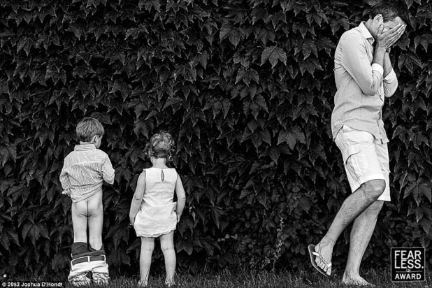 Look of disbelief:Joshua D'Hondt of Antwerp, Belgium,captured the moment a boy dropped his pants to pee in a bush while his presumed father walked away with his head in his hands