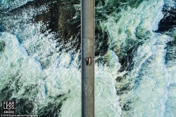 Breathtaking:Eugene Michel from Spokane, Washington, snapped a stunning photo of a couple lying on a bridge while the choppy ocean water swirls below them