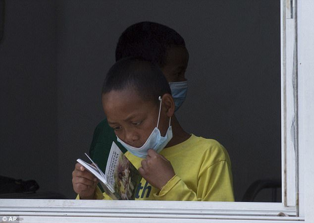 An unusually large outbreak in the country has taken 94 lives, the World Health Organization said on Friday. Pictured,a girl wears a face mask inside a hospital in the capital Antananarivo