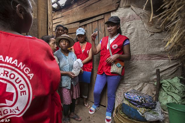 British tourists have been warned about travelling to Madagascar as an outbreak of plague has struck the paradise island leaving 90 dead. Pictured,Red Cross volunteers talk to villagers about the plague outbreak