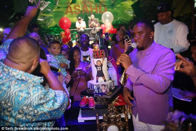 The dessert: Diddy was photographed holding a microphone to his face as he stood next to the one-year-old's elaborate three-tiered birthday cake