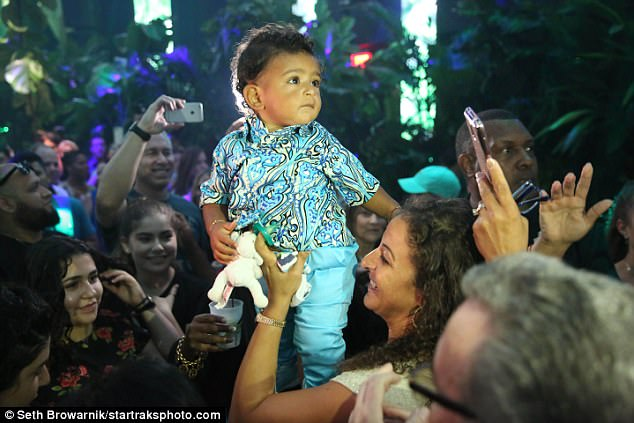 Mother and son: Nicole was also photographed holding her baby, at one point lifting him high enough that he was drifting above the crowd of partygoers