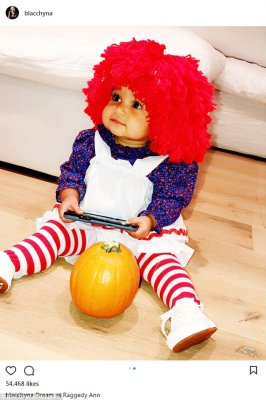 Baby's first Halloween: Wearing a tiny blue and red shirt with a crisp white pinafore dress, the little girl grinned as she played with a cell phone