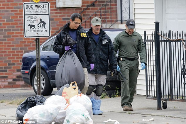 An FBI investigator carries a bag of evidence away from Saipov's home on Wednesday