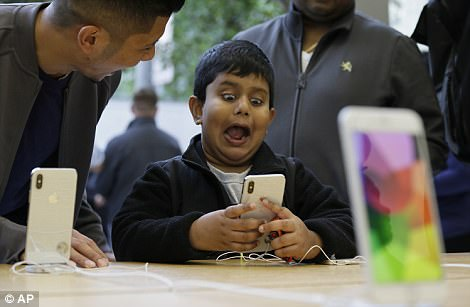 The handset went on sale around the world today, with many purchasers queueing for hours tbe among the first buyers. Pictured,Aadhyan Vaka, 6, of Plainsboro, N.J., reacts while playing with the animoji feature of the new iPhone X at the Apple Union Square store Friday, Nov. 3, 2017, in San Francisco