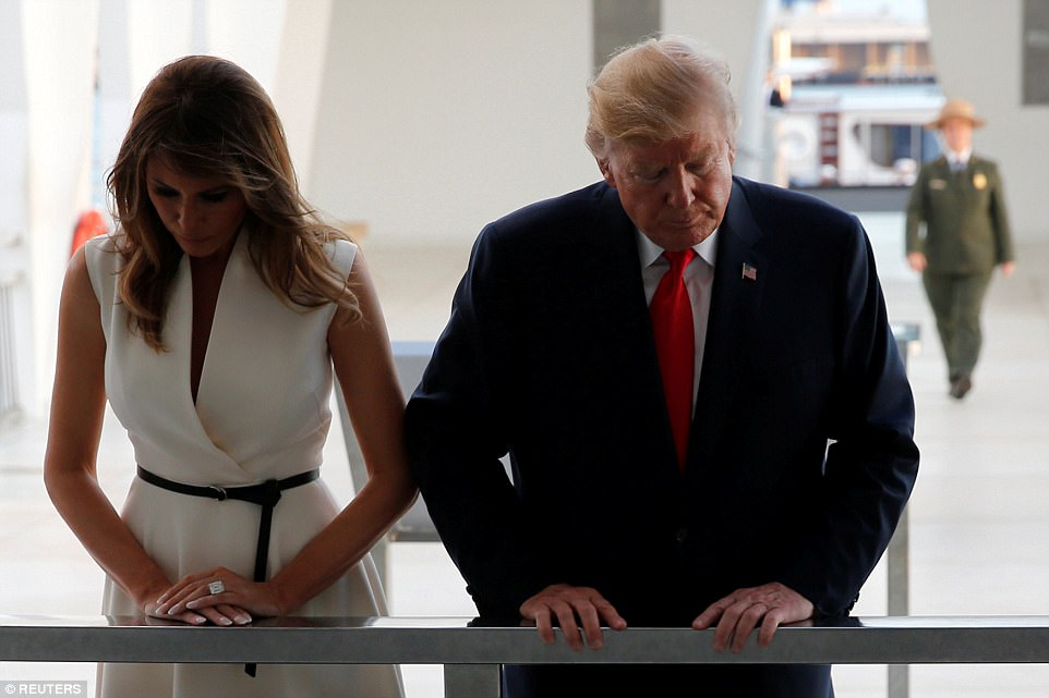 The president and first lady look down into the water at the wreckage of the USS Arizona