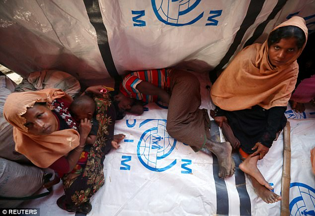 Rohingya refugees wait at a temporary shelter after crossing the border from Myanmar to Bangladesh this week