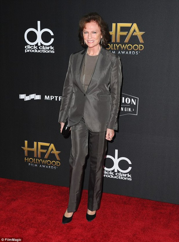Icon: Jacqueline Bisset chose a charcoal gray shiny trouser suit with a gray top and black shoes, accessorizing with a long chunky silver chain and matching earrings