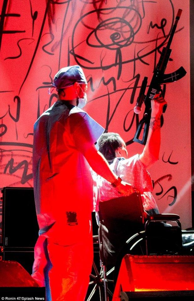 Simbolismo: Manson sostiene el rifle falso en el aire frente a la multitud de conciertos