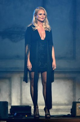 On the fringe! Lambert hit the stage in fishnet stockings and a plunging black mini dress with tassel