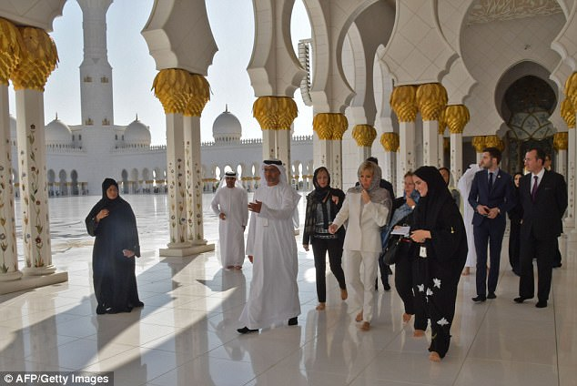 Mrs Macron listens to Emirati guides during a visit the Sheikh Zayed Grand Mosque