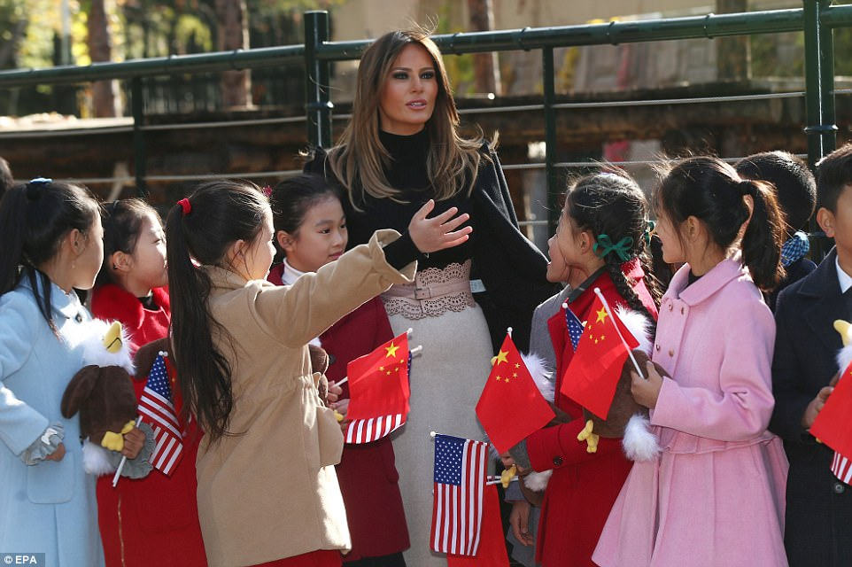 Hit with the kids: Children gathered around the First Lady waving Chinese and American flags