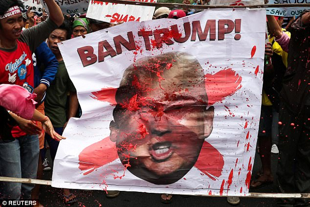 Protesters throw red paint to a picture of U.S. President Donald Trump during a rally against his visit in Manila