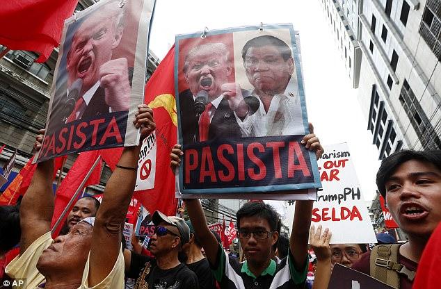 Protesters shout slogans holding portraits of U.S. President Donald Trump and Philippine President Rodrigo Duterte