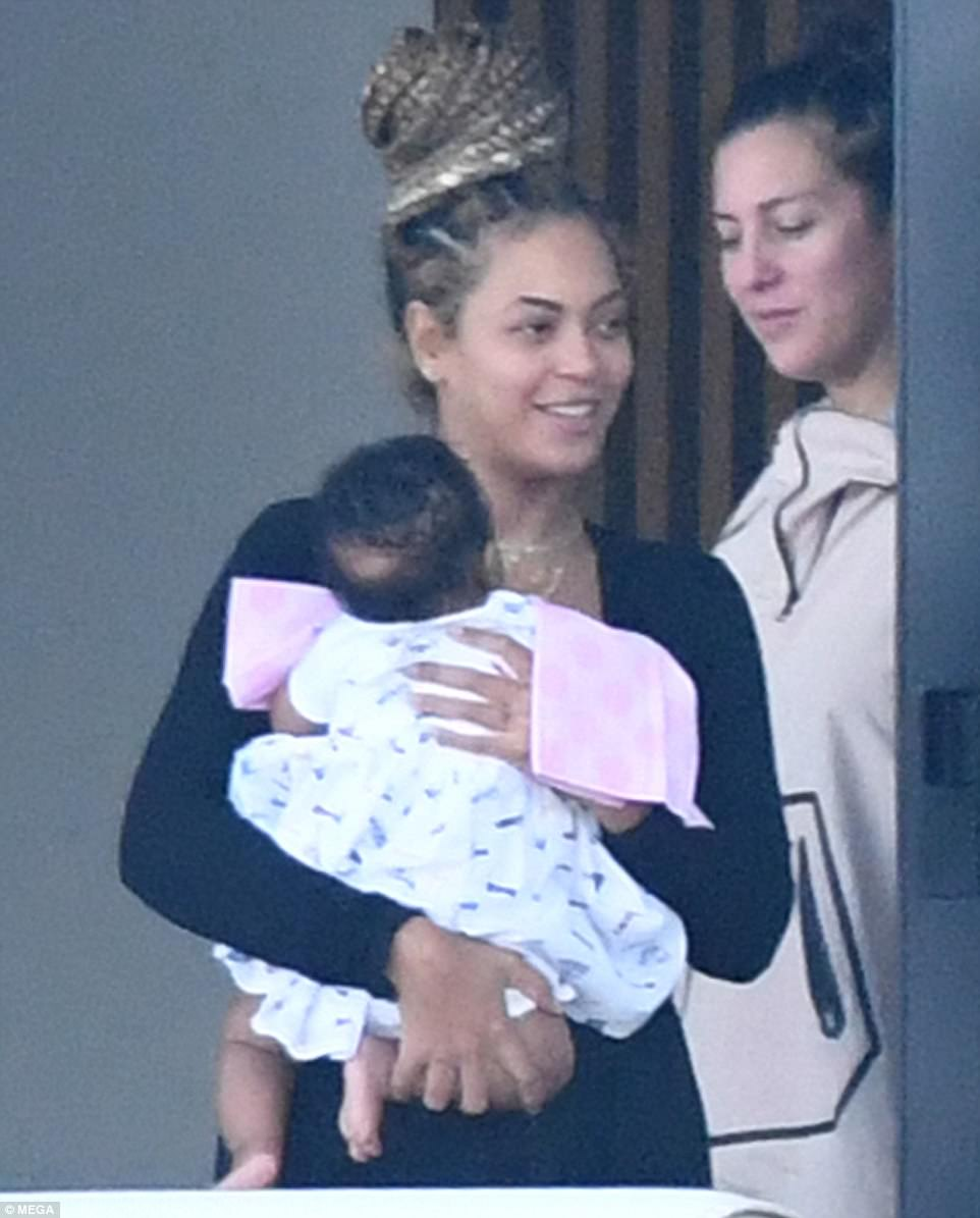 Sweet snap: Beyonce looked beautiful as she held her little girl who had pink towels around her