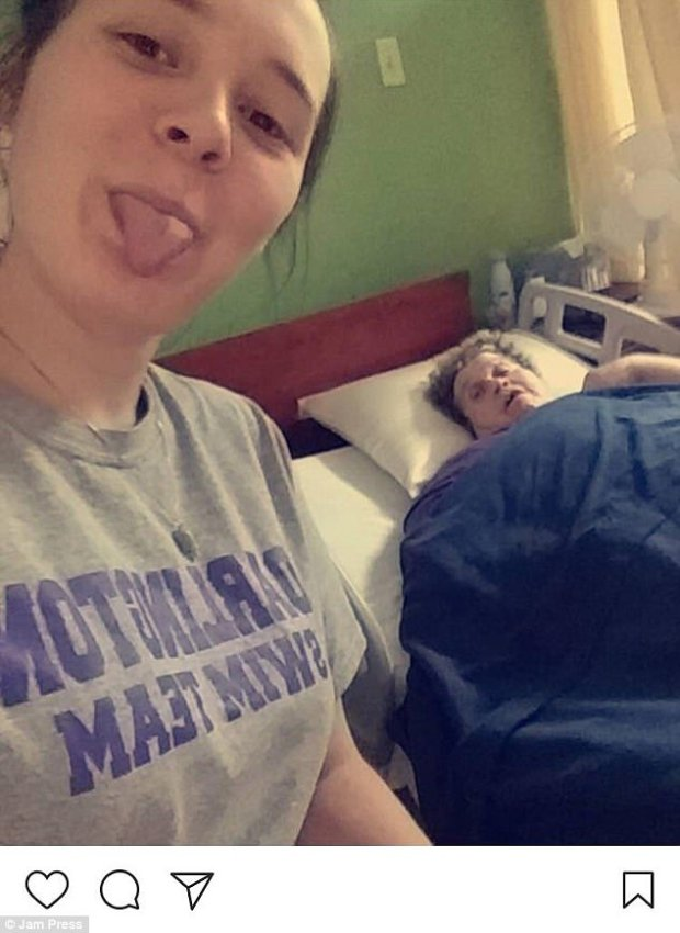 One woman stuck her tongue out in a selfie as an elderly woman lay ill in hospital behind her
