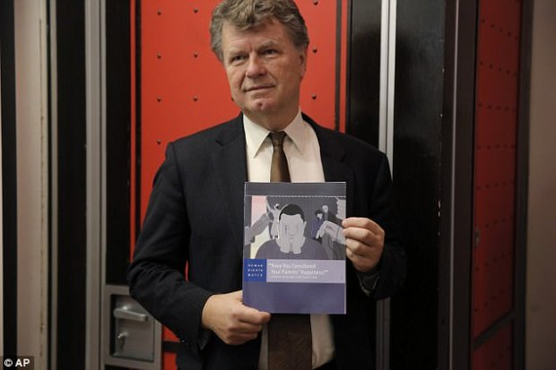Boris Dittrich, advocacy director of the lesbian, gay bisexual, and transgender (LGBT) rights program of Human Rights Watch, poses with a report in Hong Kong on Wednesday