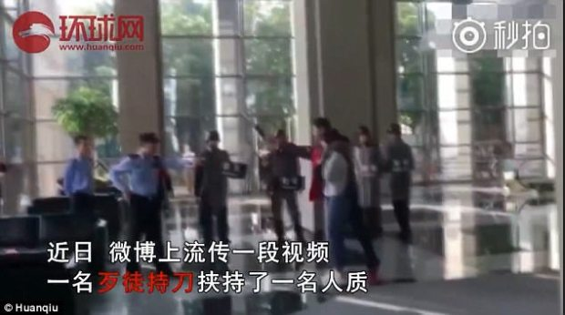 A man in red jacket is seen holding a cleaver while capturing a woman as hostage in China