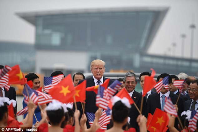 US President Donald Trump (C) watches as young girls wave US and Vietnamese national flags before boarding Air Force One to depart to the PhilippinesNovember 12, 2017