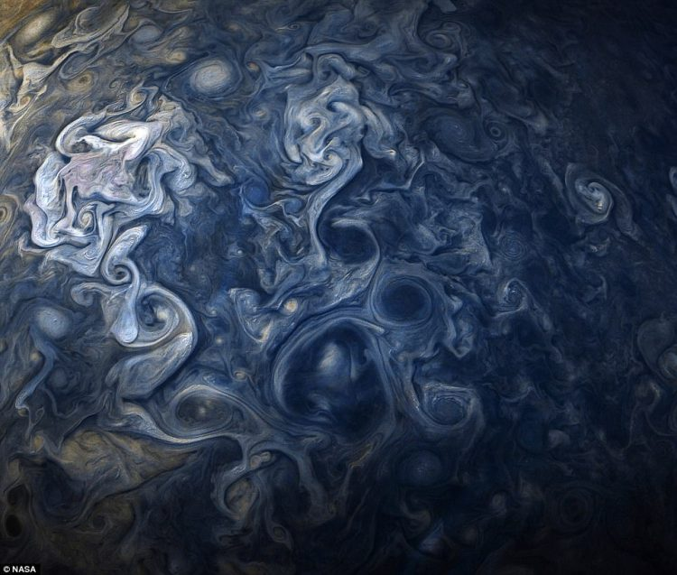 A stunning Nasa image shows raging storms on Jupiter with clouds that stretch for thousands of miles. The spacecraft captured the image, which has been colour-enhanced, while only 11,700 miles (19,000 km) from the tops of Jupiter's clouds