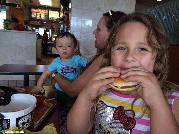 Been there: A little girl tucks into a juicy burger that's caught the eye of her little brother