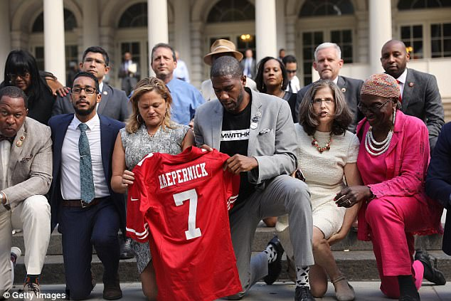 City Council Members, including Jumaane Williams (center right) and Melissa Mark-Viverto (center left) 'take a knee' on the steps of City Hall in reaction to President Donald Trump's condemnation of NFL players who do the same on September 27, 2017 in New York City