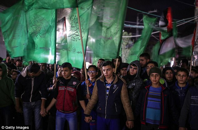 The status of Jerusalem - home to sites holy to the Muslim, Jewish and Christian religions - has been one of the thorniest issues in long-running Mideast peace efforts. Pictured: Protesters in Gaza City tonight