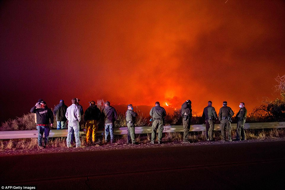 Police and fire crews watch as the Thomas Fire burns a hillside near Ojai. That town was evacuated after it was surrounded by fire overnight. Experts worry that firefighters will only be able to watch if winds whip the fire out of control on Thursday