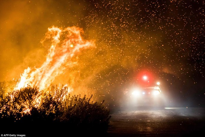 A fire truck drives through a shower of sparks on the 101 Highway on Thursday morning as the Thomas Fire continues to raze vast swathes of countryside. There is concern that wind will blow these sparks far away, causing further damage