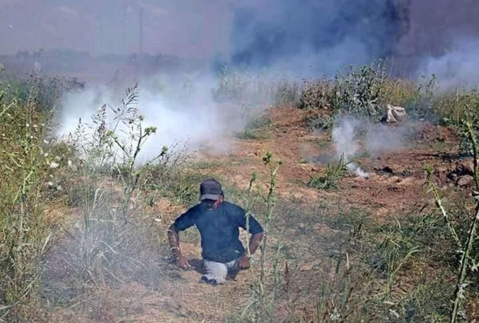 Pictured: Ibrahim Abu Thurayeh, 29, can be seen moving through smoke-filled grassland during clashes in Gaza City, Palestine today
