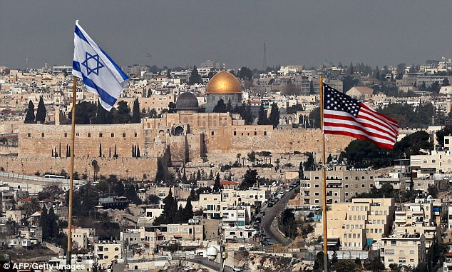 It is not clear how he would carry out the move, as Israel controls all of Jerusalem (pictured), calling the city its indivisible capital. The US and Israeli flags are pictured flying on the roof of an Israeli settlement in East Jerusalem