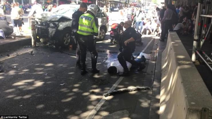 Two men were arrested at the scene after the white SUV (pictured) crashed into a bollard at Flinders Street Station