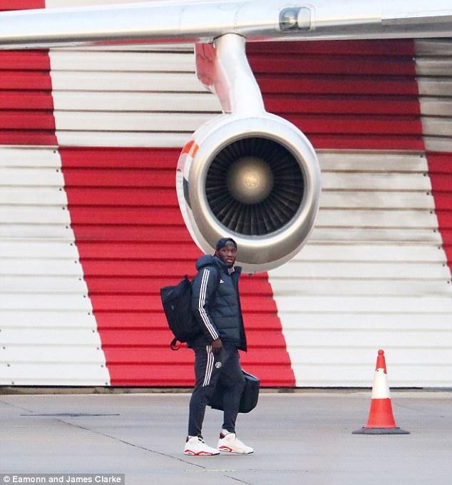 Romelu Lukaku looks on as he makes his way across the runway and on to the team plane