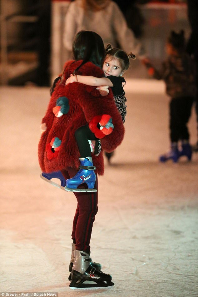 Sweetheart: Little Penelope seemed too tired to make it across the rink and was carried off the ice by her strong mother