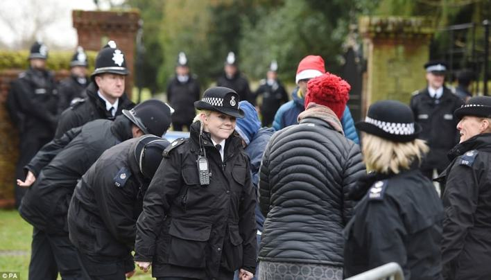 A small army of police officers were at the Sandringham estate this morning ahead of the royal arrivals; a female officer raises a smile as she chats with one of the many people gathered to catch a glimpse of the family as they arrive for church