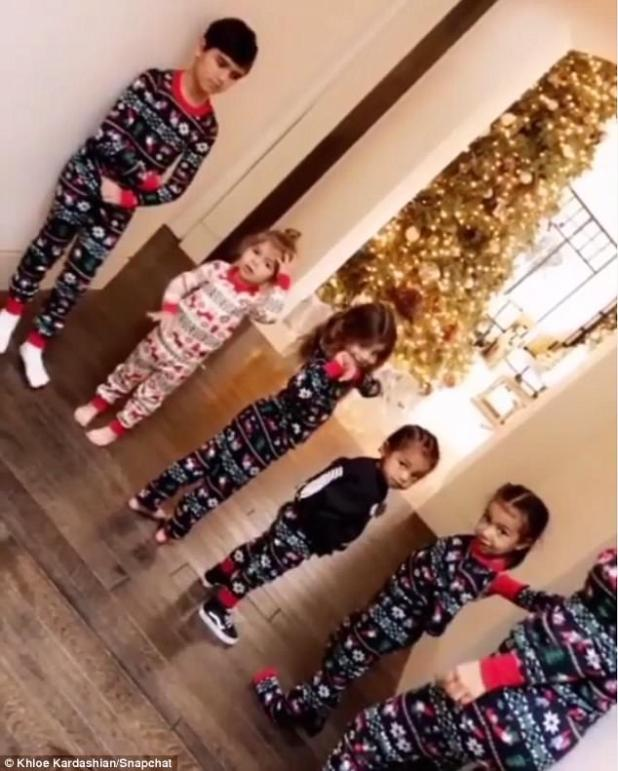 Before gifts:They were seen standing in a hallway before they were allowed to run to the living room where their gifts from Santa waited.Also with them were Mason and Reign, the children of Kourtney. It looked like they had another little friend with them too