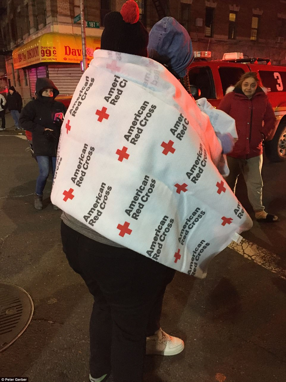 One family was seen wrapped in an American Red Cross blanket after escaping the blaze