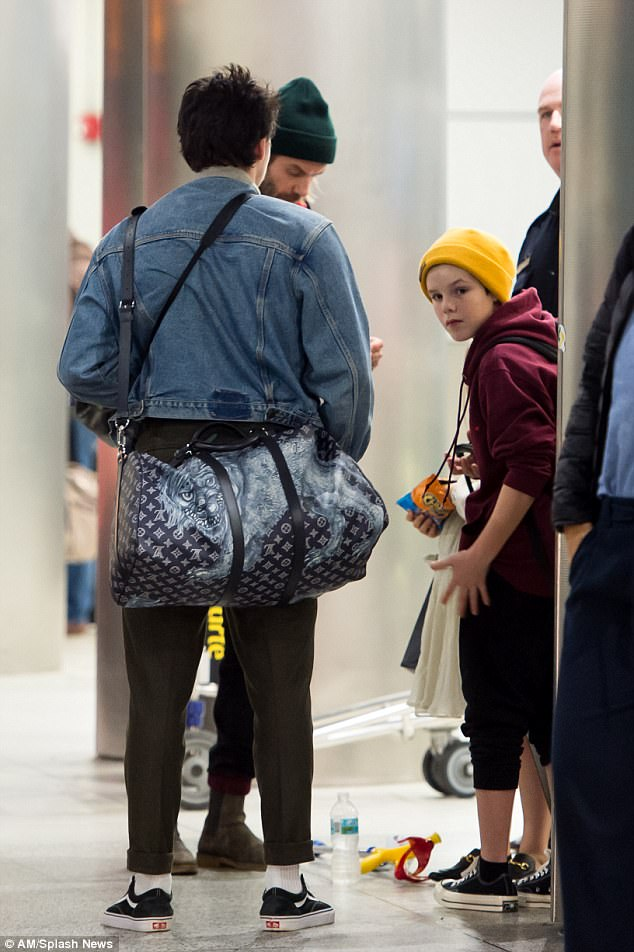 Preppy: Their eldest son, Brooklyn looked effortlessly cool in a denim jacket and khaki chinos as he slung a Louis Vuitton holdall over his shoulders