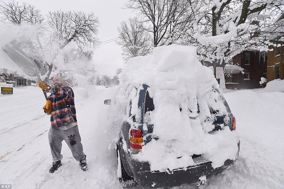 Kevin Deiner of Erie digs out his Ford Escape buried on West Sixth Street also on Saturday
