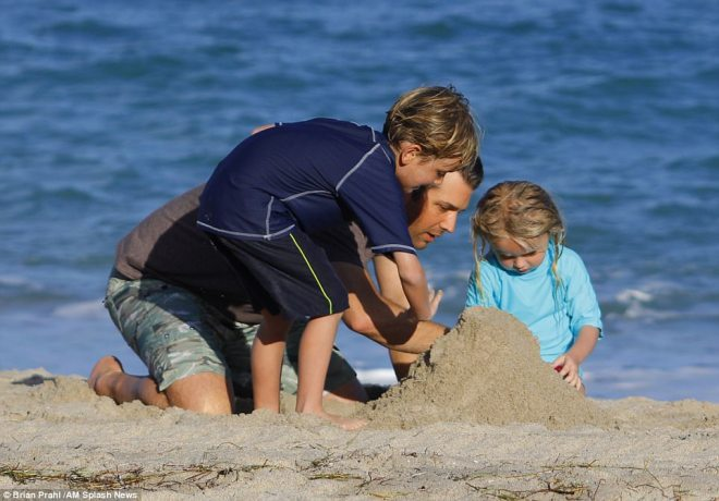 Don Jr. was all smiles as he got on his knees to get in on the fun and build a sand castle with them on the final day of the year