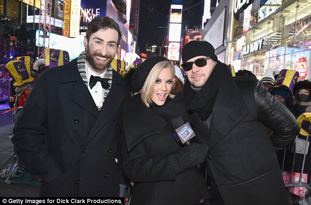 Bundled up: She later donned a black overcoat that matched her husband's as they posed for photos with trivia host Scott Rogowsky