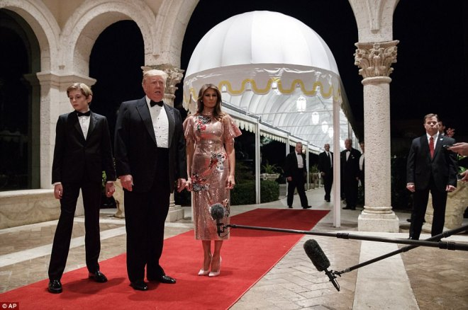 President Donald Trump speaks with reporters as he arrives for a New Year's Eve gala at his Mar-a-Lago resort with first lady Melania Trump and their son Barron, Sunday, Dec. 31, 2017, in Palm Beach, Florida
