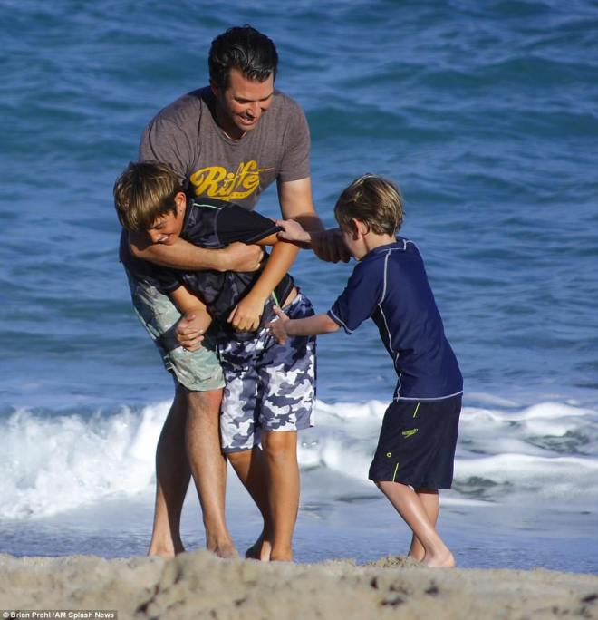 The family played in the sand as they sported shorts and tees for the warm day on the beach