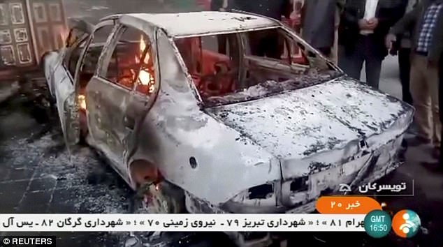 Six of the most recent decent deaths happened when protesters clashed with security forces as they tried to storm a police station in Qahderijan, a town of 30,000 in the Isfahan region of central Iran. People stand near a burning car in Tuyserkan, Hamadan Province, Iran on December 31