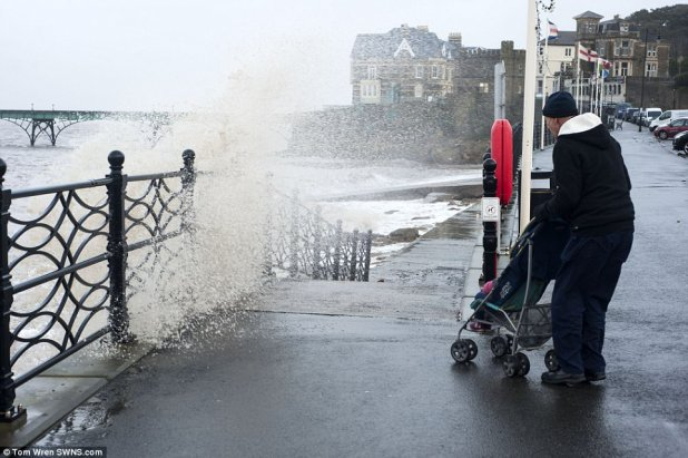 A man with a pushchair narrowly avoids a soaking as a wave crashes in opposition to the sea wall in Clevedon this morning